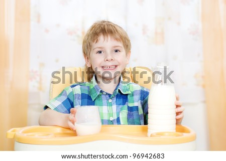 child drinking milk. Holding glass of milk and sitting at the table.
