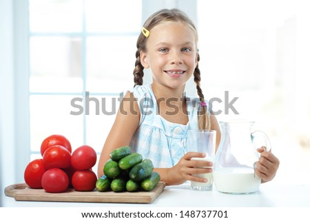 Child drinking milk in the kitchen at home - stock photo