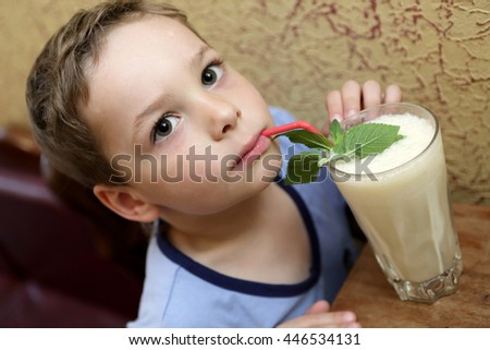 Child drinking milk shake in a cafe - stock photo