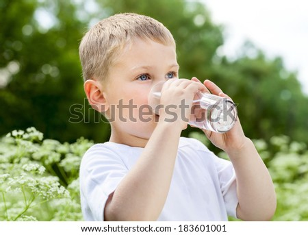 Child drinking pure water in the nature - stock photo