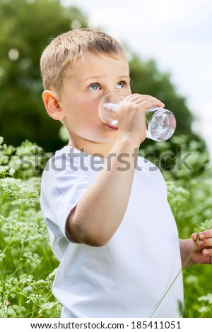 Child drinking pure water in the nature