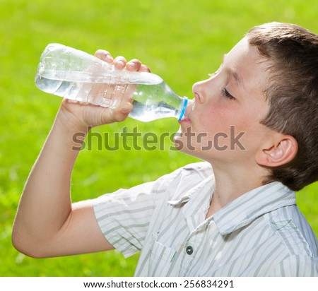 Child drinking water. Boyl outdoors - stock photo