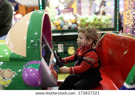 Child driving car toy at an amusement park - stock photo