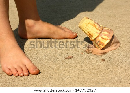 Child Drops Ice Cream Cone by Feet - stock photo