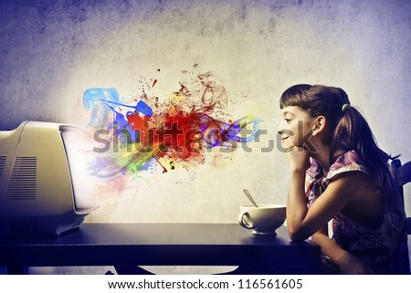 Child, during the breakfast, watching a TV from which come out of the colors - stock photo