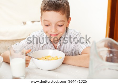 Child eat breakfast. Boy eating cereals with milk - stock photo