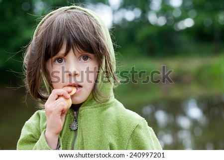 Child eating a biscuit outdoors nature