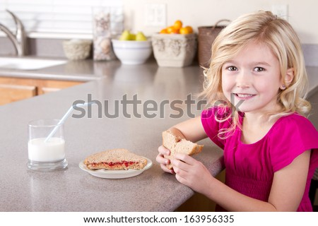 Child eating a peanut butter and jelly sandwich sitting at table in kitchen at home - stock photo