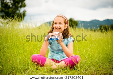 Child eating and relishing chocolate - outdoor in nature