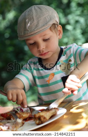 Child eating chicken in the outdoor cafe - stock photo