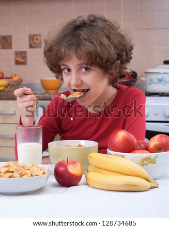 Child eating cornflakes on the kitchen - stock photo