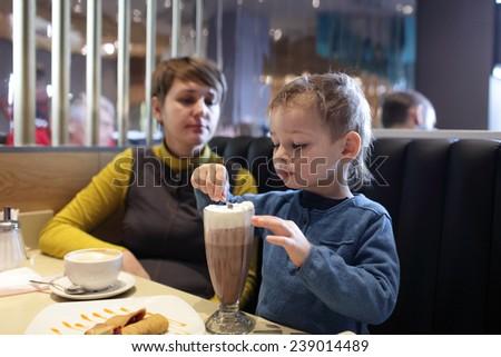 Child eating foam of milkshake in the restaurant - stock photo