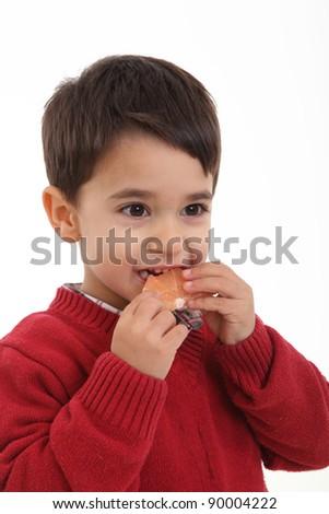 Child eating grapefruit on white background - stock photo