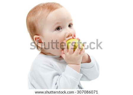 Child eating green apple toys in a blue dress. Studio Half Length Portrait , isolated on a white background