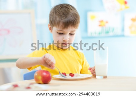 child eating healthy food at home or kindergarten - stock photo