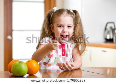 child eating healthy food in kitchen - stock photo
