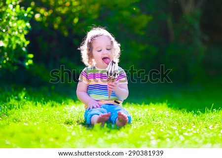 Child eating ice cream. Kids play outdoors enjoying sweet snack on a hot summer day. Children eat icecream. Toddler kid playing in the garden. Little girl with vanilla and chocolate ice cone. - stock photo