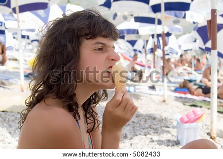 Child eating ice cream on the beach - stock photo