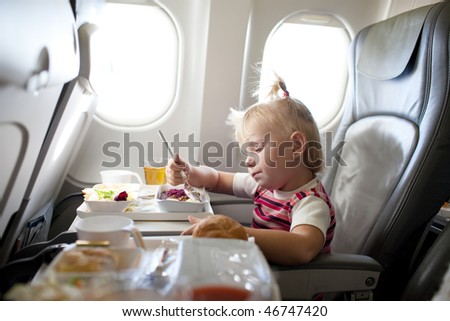 child eating in the airplane - stock photo