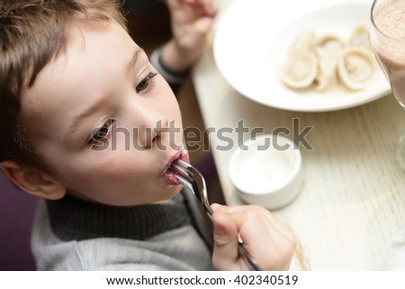 Child eating meat dumplings in a cafe