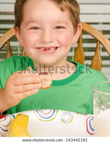 Child eating messy peanut butter and jelly sandwich with milk and fruit for healthy lunch - stock photo