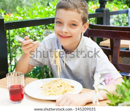 Child eating pasta in cafe. Boy eating spaghetti. Food - stock photo