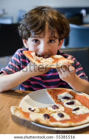 child eating pizza in restaurant - stock photo