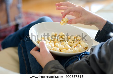 Child eating popcorn while watching a film maybe, showing just bowl of popcorn in lap - stock photo