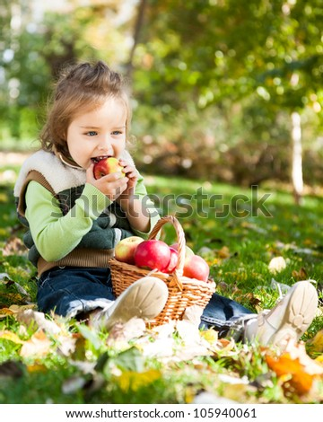 Child eating red apple in autumn park - stock photo