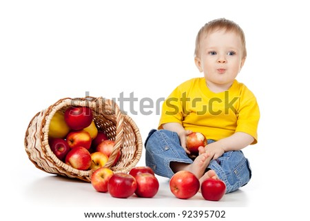 child eating red apples;  near basket - stock photo