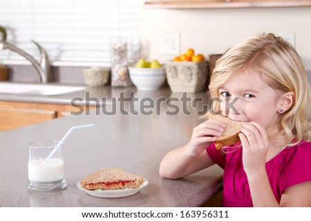 Child eating sliced apples sitting at table in kitchen