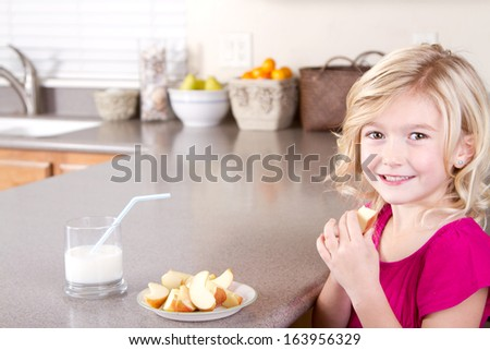 Child eating sliced apples sitting at table in kitchen - stock photo