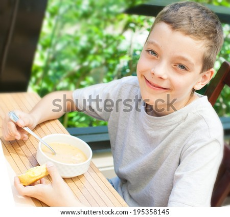 Child eating soup at cafe - stock photo