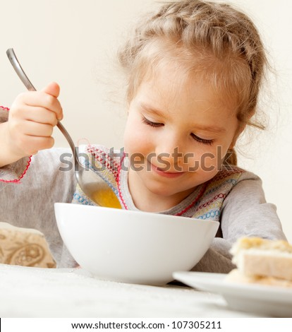 Child eating soup at home. Little girl have a dinner - stock photo