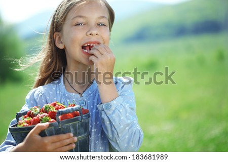 Child eating strawberries in a spring floral field - stock photo
