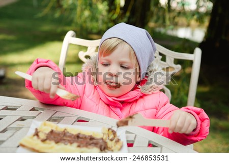 Child eating waffles with chocolate in a spring park - stock photo