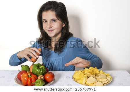 Child eats fresh vegetables - refuse potato chips - stock photo
