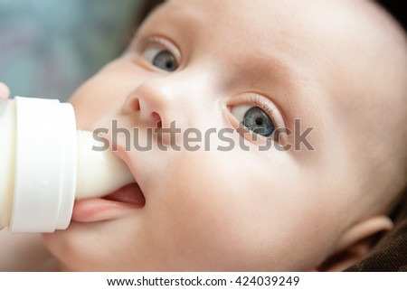 Child eats from a bottle. Artificial feeding. - stock photo