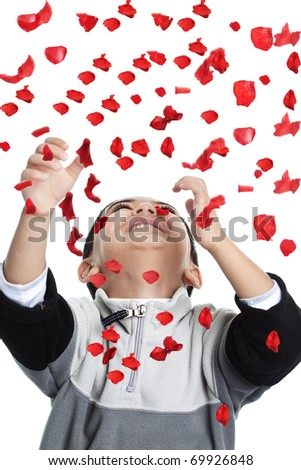 Child Enjoying a Shower of Red Rose Petals, Isolated, White - stock photo