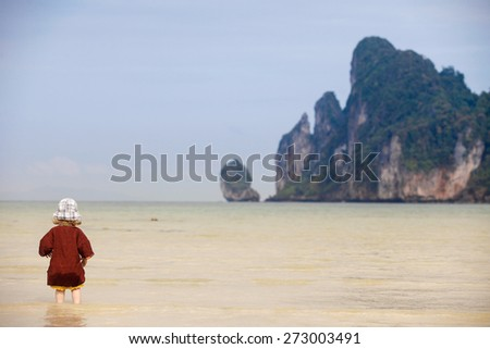 Child enjoying the low tides, walking on fine sand through the water on a tropical beach. Fearless, intrepid and adventurous childhood concept.   - stock photo