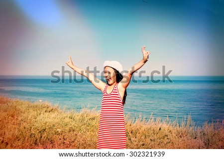 child enjoying the sea, arms raised - stock photo