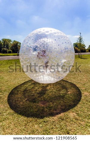 child enjoys rolling the zorbing ball - stock photo