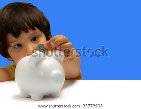 child entering a coin in a piggy bank - stock photo