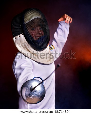 Child epee fencing lunge. Dark background. - stock photo