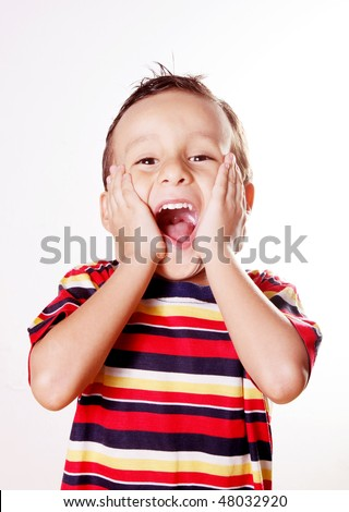 Child expressing surprise and happiness with his hands in his face - stock photo