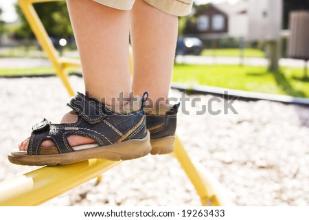 Child feet on a ladder in a playground - stock photo
