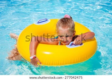 Child female on inflatable yellow ring in swimming pool. - stock photo