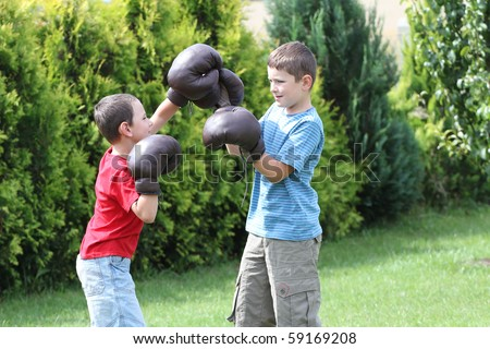 Child fighting with boxing gloves. Sibling, two boys boxing. - stock photo