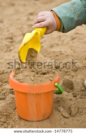 child filling plastic children bucket with sand - stock photo