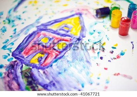 Child fingerpainting of a house in vivid colors - stock photo